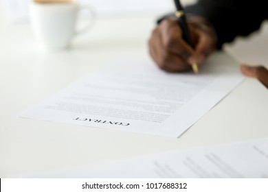 Contract close up view, african american businessman signing business legal paper concept, black man agree on terms and conditions taking contractual obligations putting signature, focus on document