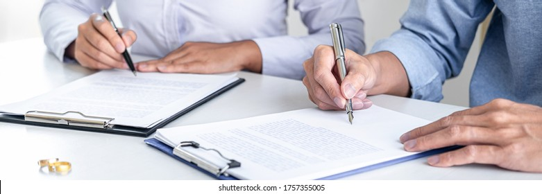 Contract decree of divorce (dissolution or cancellation) of marriage, husband and wife during divorce process and signing of divorce contract, Wedding ring.