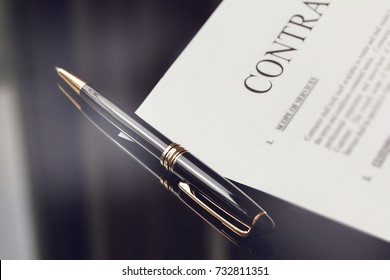 contract documents and fountain pen on black office desk, successful business concepts