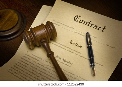 Contract on a wooden desk with a gavel and fountain pen