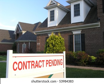 contract pending sign in front of a new house