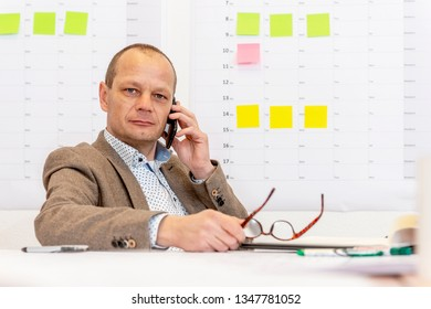 Contracting managing partner on the phone at this desk, holding his reading glasses with a planning board on the wall behind him