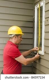 contractor carpenter measuring window for replacement repair