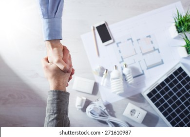 Contractor and customer shaking hands close up, energy saving CFL lamps, solar panel and house draft project on background, top view