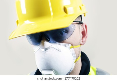 Contractor Face Closeup. Contractor in Safety Glasses, Yellow Helmet and Breathing Safety Mask.