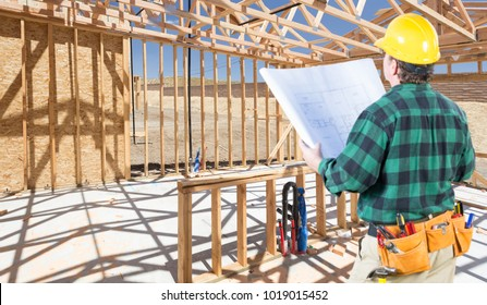 Contractor with hard Hat and Plans Standing Inside Construction Framing of New House.