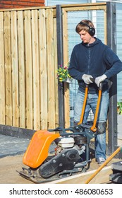 Contractor in headphones using a vibratory plate compactor to make the soil flat before paving