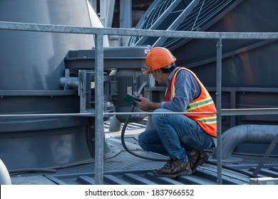 Contractor inspection installation equipment on site construction. worker open valve of cooling tower on blue sky background. worker opening butterfly valve on top of cooling Tower.