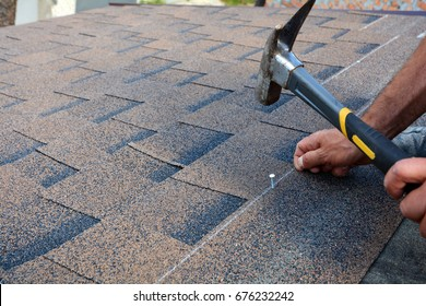 Contractor installing bitumen roof shingles with hammer and nails.