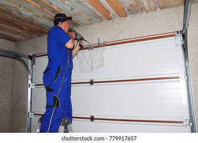 Contractor installing garage door and drilling hole for garage door opener.