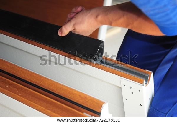 Contractor installing garage door weatherproofing garage door seal. Replace Garage Door Seal.