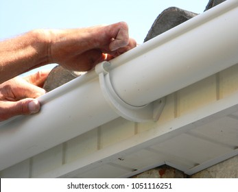 Contractor installing plastic roof gutter. Plastic Roof Guttering Renovation, Rain Guttering Repair & Drainage by Handyman hands.