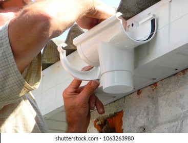Contractor installing plastic roof gutter holder for dowspout drain pipe. Plastic Roof Guttering, Rain Guttering & Drainage by Handyman hands.
