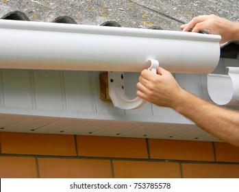 Contractor installing plastic roof gutter. Plastic Guttering, Rain Guttering & Drainage by Handyman hands.