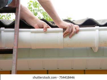 Contractor installing plastic roof gutter pipeline. Roofer Install Rain gutter.