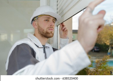 Contractor looking at window roller shutter