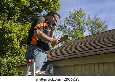 Contractor on ladder with cell phone figuring out hail damage repair costs for customer.