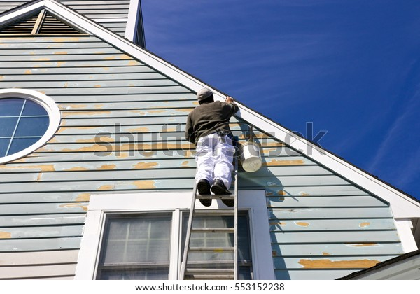 A contractor or painter on a ladder doing exterior paint work, sanding, trim work and repairs on a house, condo or building with wood siding. Blue sky background. Urban city environment.