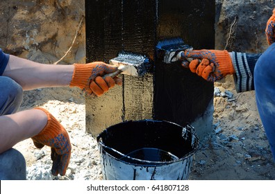 Contractor painting black coal tar or bitumen at concrete surface by the brush, a foundation Waterproofing for anti damp proofing.