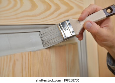 Contractor painting a wooden door
