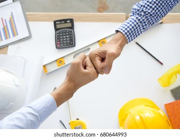 Contractor successfull teamwork. Engineer and architect partners giving fist bump after complete deal.