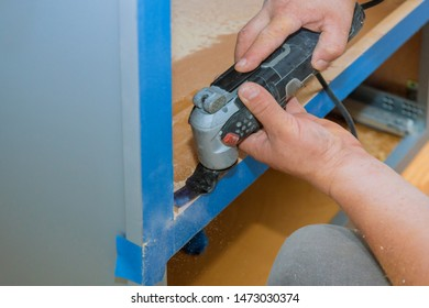 Contractor using electric oscillating multi functional cutting tool for handyman cut hole in kitchen furniture