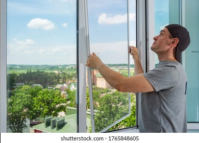 A contractor worker installing mosquito wire screen on house plastic windows to protect from insects. - Shutterstock ID 1765848605