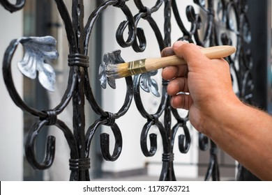 Contractor's hand with brush that painting metal fence.