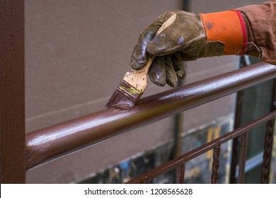 Contractor's hand with brush that painting metal railing construction.