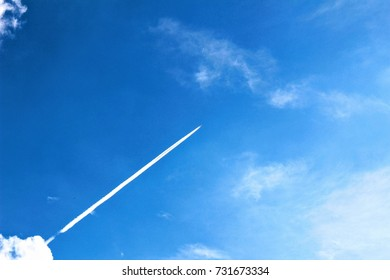 Contrail from an airplane flying over a clear blue sky.
