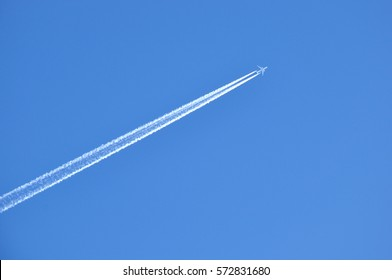 contrail of overflying passenger airplane in the clear blue sky