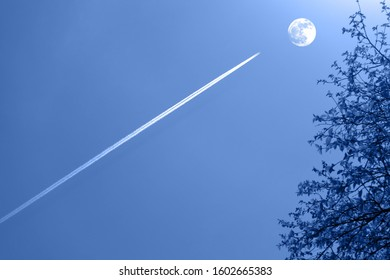 Contrail produced by flying aircraft  against the clear blue sky aiming at the day moon. Through hardships to the stars concept