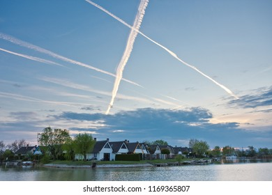 Contrails in blue evening sky forming a big X over terraced cottage settlement on Lake Neusiedlersee in Burgenland.