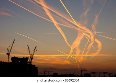 Contrails crossing each other. Congested airspace over Frankfurt, Germany, at sunrise.