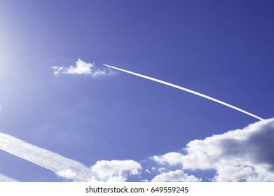 Contrails from a jet plane on blue sky background. Aircraft flying on airway bypasses the rain clouds.