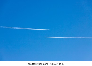 Contrails of two airplane flying on a opposite course, Aircraft with waste smoke trails, Vapour trails after a large commercial jet plane high in blue sky background.