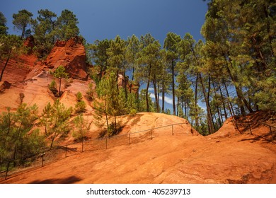 Contrast between the green pine trees and yellow ocher soil. Unique red and orange hills in Roussillon, France