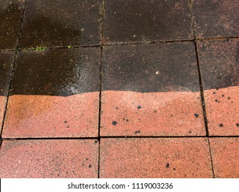 Contrast between patio paving slabs which have been pressured washed. The clean slabs are red and the dirty unwashed slabs are at the top of the image