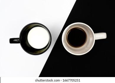 the contrast of a cup of coffee and a cup of milk