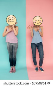 Contrast. Full length of sad lady standing on blue background and her happy friend on pink one