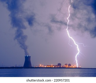 A contrast photograph of the power of mother nature and man-made energy; A lightning bolt striking the water in take area of a nuclear power plant.