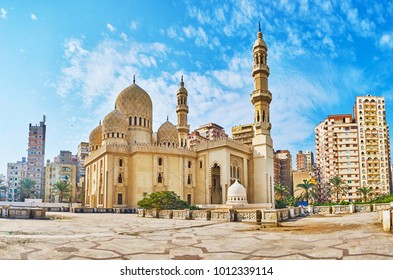 The contrast of the scenic Sidi Yaqut al-Arshi mosque, decorated with carved islamic patterns and the modern multistory living neighborhood, seen on background, Alexandria, Egypt.