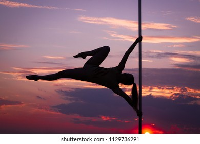 Contrast silhouette photos at sunset against the sky: girl poledancer performs an element on the pole with the bend in the back