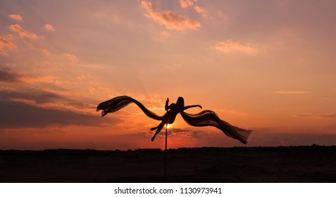Contrast silhouette photos at sunset against the sky: girl poledancer performs an element on the pole with wings and beautiful flying, flowing fabric