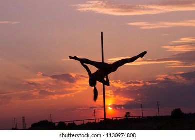 Contrast silhouette photos at sunset against the sky: girl poledancer performs an element on the pole with the split