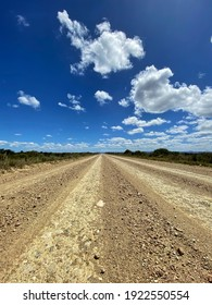Contrasting colours between the open dirt road and the bright blue sky.