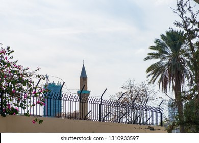 Contrasting view of a palm tree, a mosque and a sky scraper viewed from the histtoric center of Nicosia, Cyprus