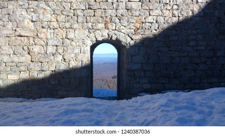Contrasting winter image of snow, shadow on an ancient stone wall, and view through an archway onto French Pyrenean landscape under bright blue sky at Montsegur Cathar castle in the Ariege, France