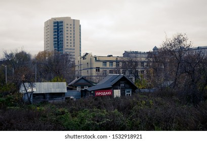 "Contrasts of Russian cities - new buildings, and in front of them falling apart old houses with the inscription ""sell"""
