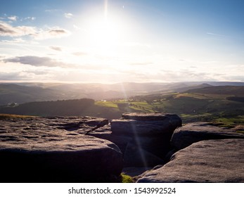 Contre jour image of sunset at Stanage Edge, Peak District UK, with rock outcrop in the foreground and rolling fields in the background.